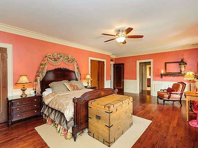 Traditional bedroom with pink walls above white wainscoting and rich hardwood flooring topped by a beige rug. It features a gorgeous skirted bed designed with green and pink striped valance.