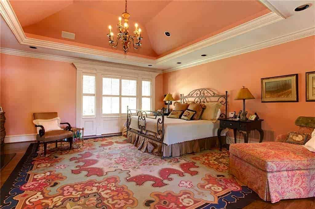 Pink bedroom illuminated by a candle chandelier that hung from the tray ceiling. It has an ornate bed accompanied by a skirted chaise lounge and a brown armchair over a lovely area rug.