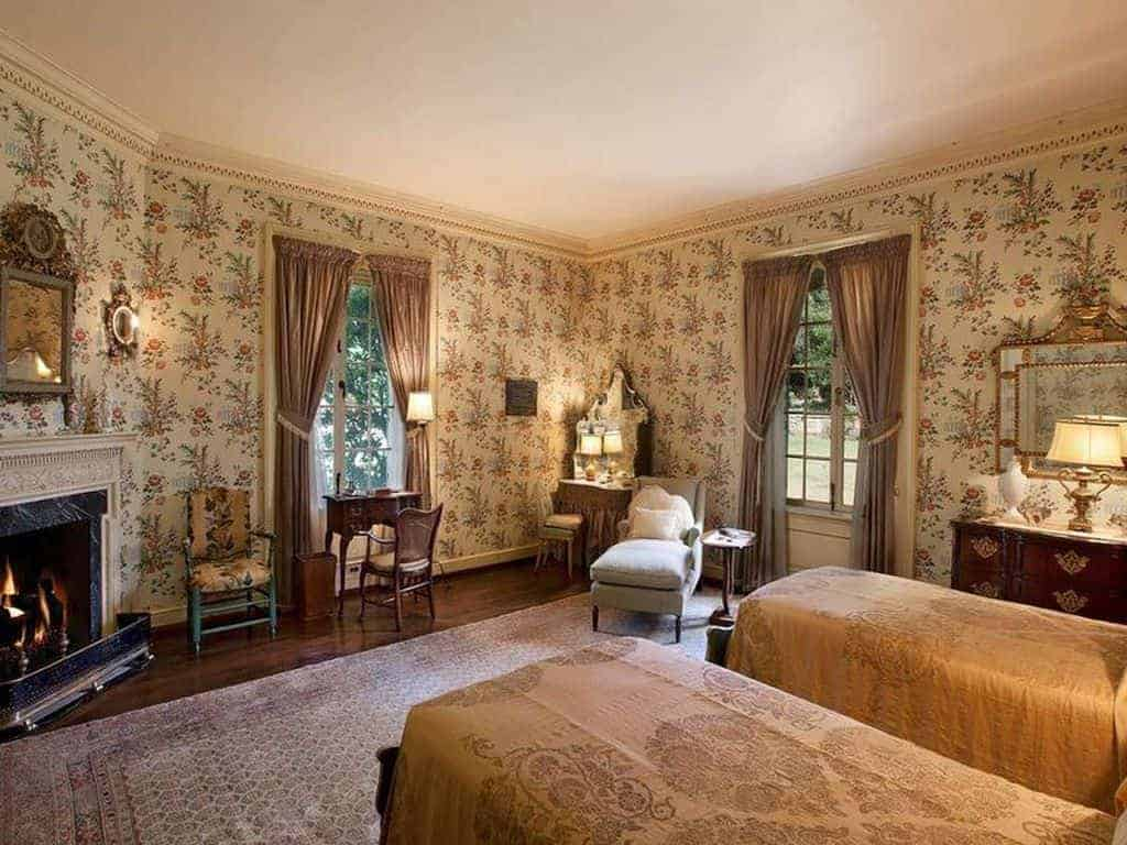 Classic traditional bedroom showcases dark hardwood flooring topped by a vintage rug and a lovely floral wallpaper lined with an ornate crown molding.
