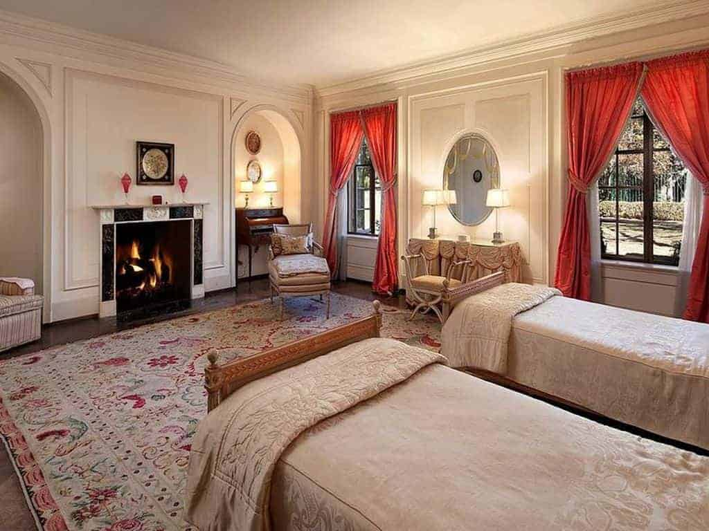 Gorgeous bedroom accented by red drapes and a charming floral rug that lays on marble flooring. It features a stylish black fireplace fixed in between arched inset walls.