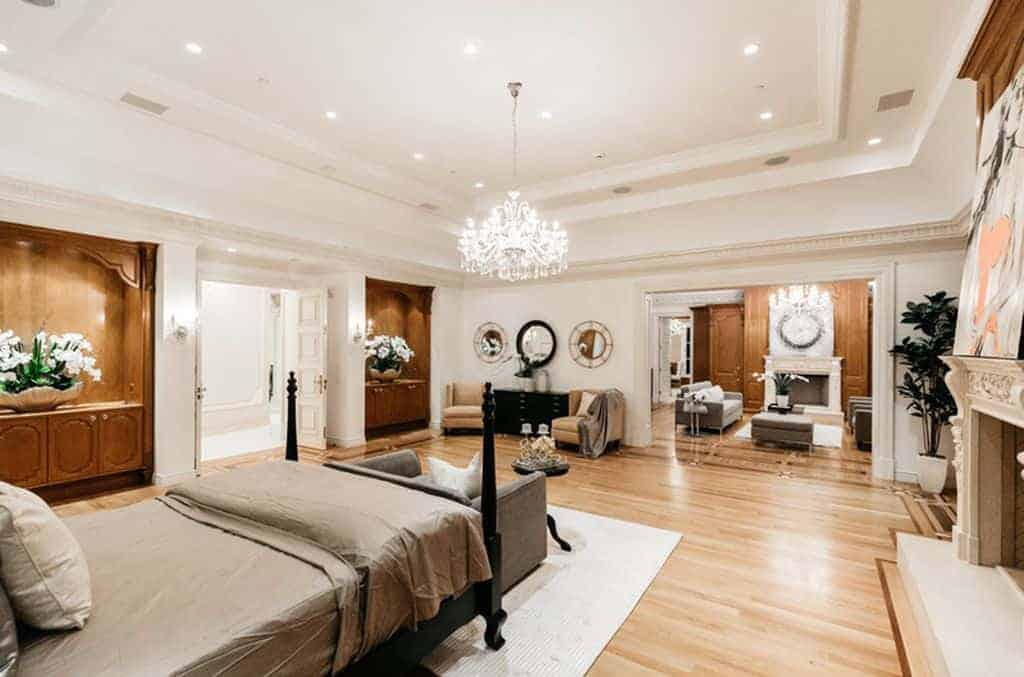 Luxury bedroom with a dark wood four poster bed and a spacious seating area from the adjoining room lighted by crystal chandeliers that hung from the tray ceiling.