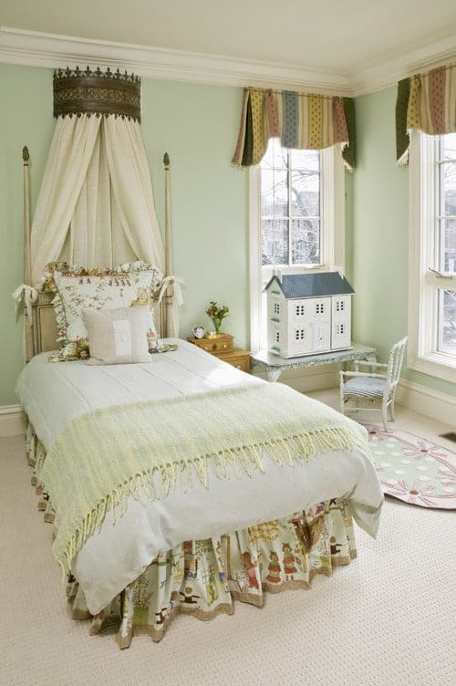 A round canopy hangs over the gorgeous skirted bed in this mint green bedroom with carpet flooring and white framed windows dressed in striped valances.