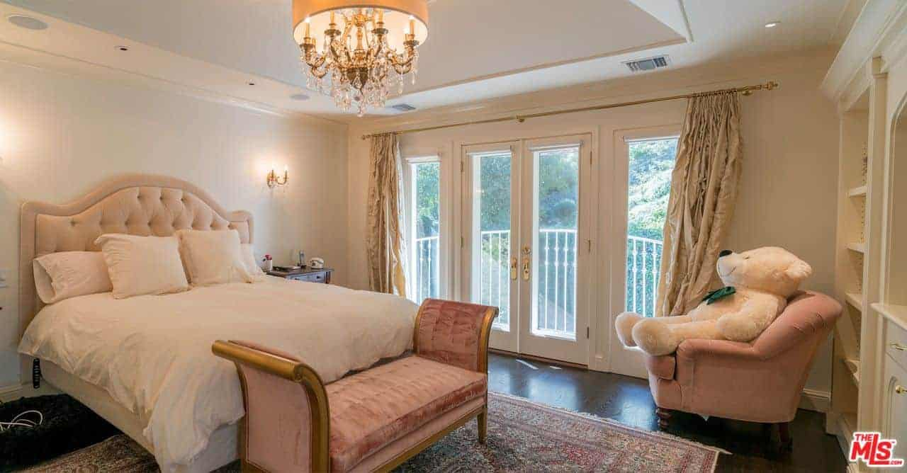 A cute teddy bear sits on a blush armchair in this kids bedroom illuminated by a glam chandelier that hung over the beige tufted bed and Cleopatra seat.