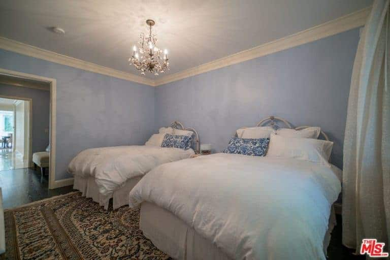 Traditional blue bedroom with two skirted beds on a vintage rug over dark hardwood flooring lighted by a candle chandelier.