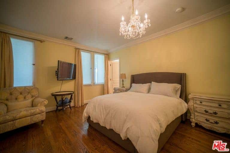 Warm bedroom showcases a crystal chandelier that hung over the brown bed dressed in white bedding. It is accompanied by ornate nightstands and a tufted seat by the glazed window.