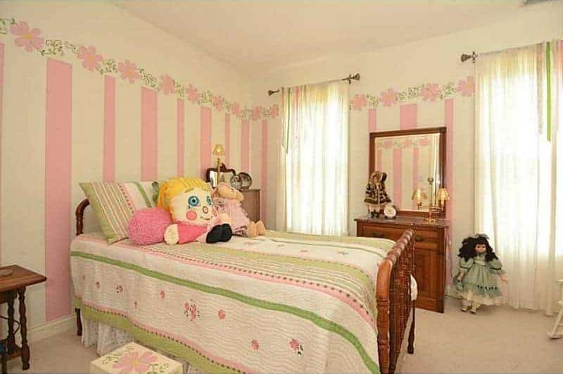 Green striped bed and pillow create a nice contrast with the floral and pink striped wall in this bedroom with wooden vanity and various dolls.