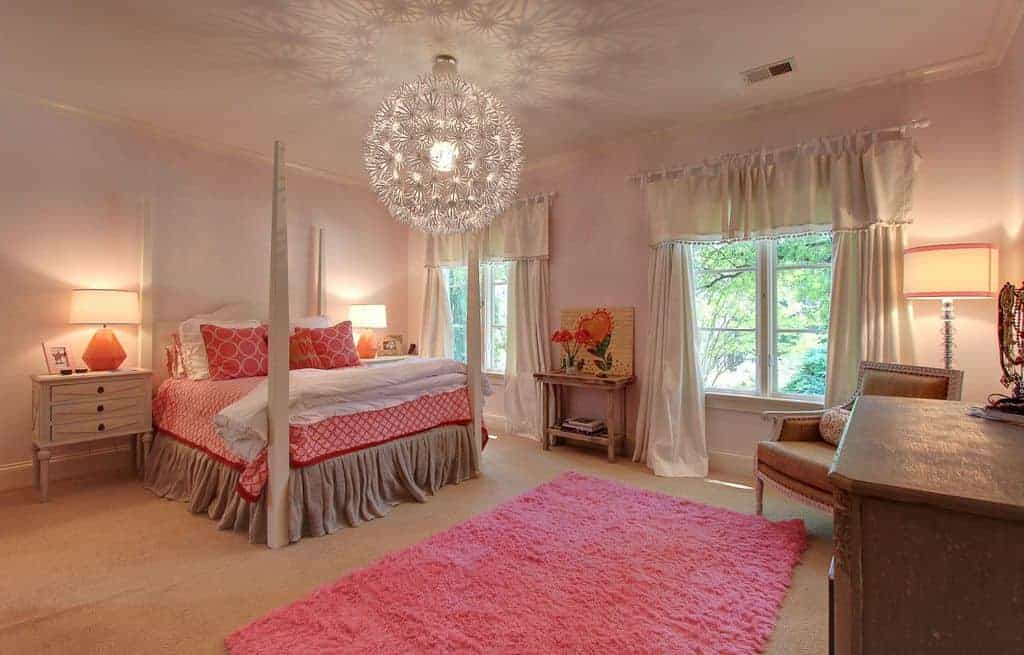 Gorgeous kids bedroom with white framed windows and carpet flooring topped by a pink shaggy rug. It has a four poster bed lighted by a spherical chandelier and table lamps.