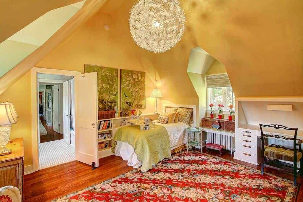 A spherical chandelier illuminates this kids bedroom painted in mustard yellow. It has a built-in bed and desk with an alcove seat nook in the middle.