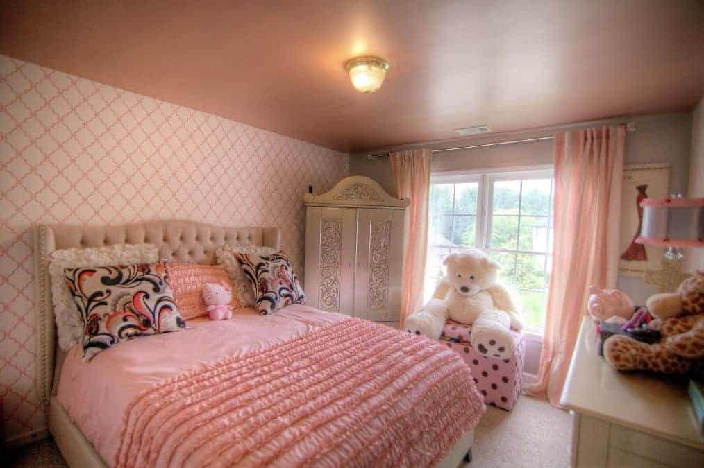 Pink bedroom offers beige tufted bed and an ornate wardrobe next to the white framed window covered in striped draperies.
