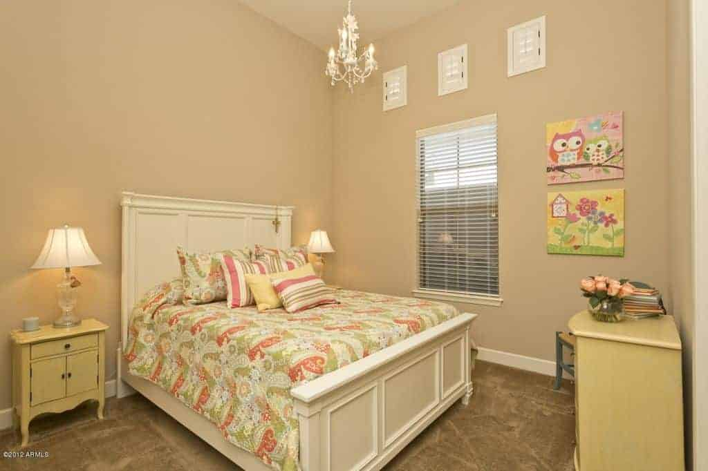 Traditional kids bedroom decorated with lovely wall arts and a crystal chandelier that hung over the white bed dressed in green patterned bedding.