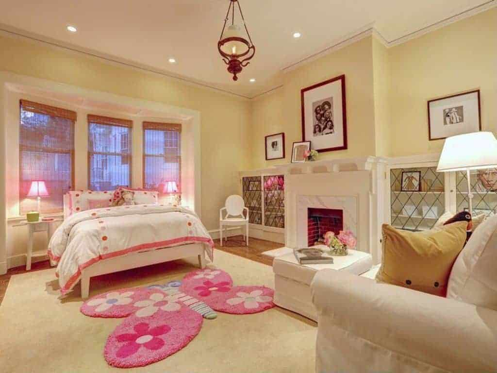 Charming girls bedroom features a fireplace with white marble surround tiles in between built-in cabinets enclosed in crisscross doors. It includes comfy bed and seats and a pink butterfly rug on a beige velvet rug.