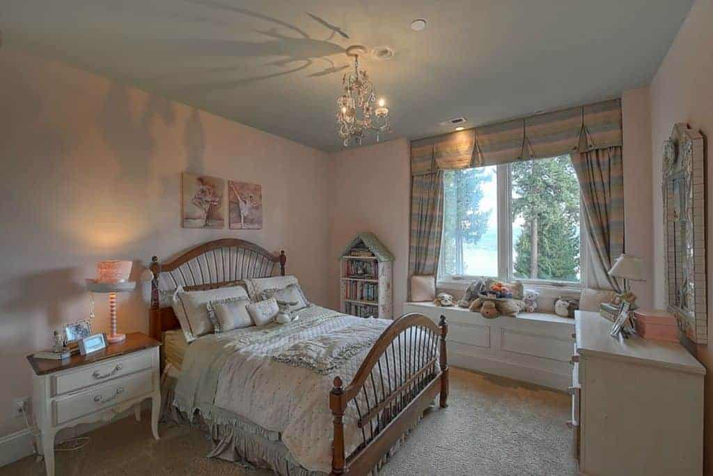 Striped drapes and valance cover the glazed windows in this kids bedroom with lovely wall arts and cute stuffed toys sitting on the built-in seat nook.