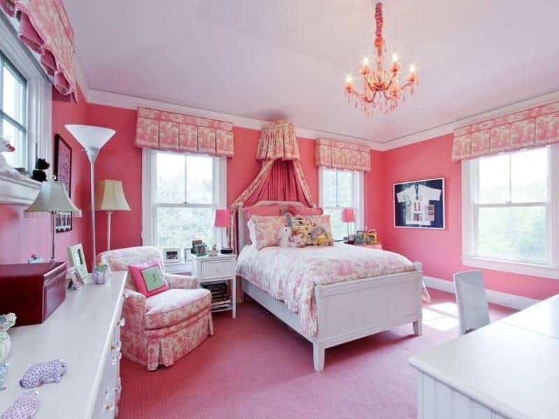 Pink girls bedroom with a skirted seat that complements with the valances and bedding wrapping the white bed. It is illuminated by a glamorous chandelier along with natural light from the white framed windows.