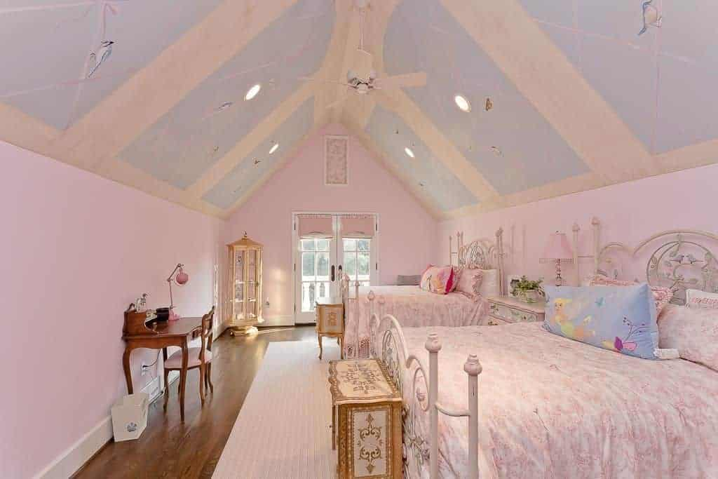 Charming shared bedroom features hardwood flooring topped by a pink area rug and cathedral ceiling painted with lovely birds on a blue background.