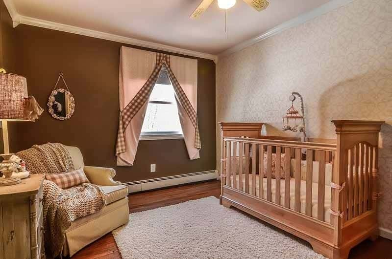 This nursery bedroom offers a wooden crib on a gray shaggy rug and a skirted armchair beside the dresser topped with a table lamp.