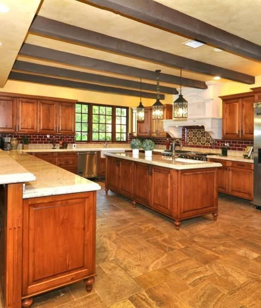 Warm kitchen with limestone flooring and mustard yellow ceiling lined with exposed beams. It includes stylish pendant lights and wooden cabinetry accented with red brick backsplash tiles.