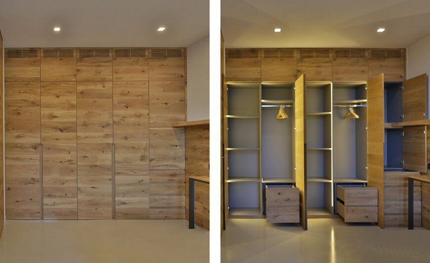 This modern closet features a wooden cabinetry with lights installed inside. The flooring looks great with the room's style.