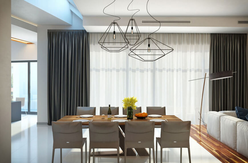 Modern dining area with a stylish dining table set lighted by a gorgeous set of ceiling lights.