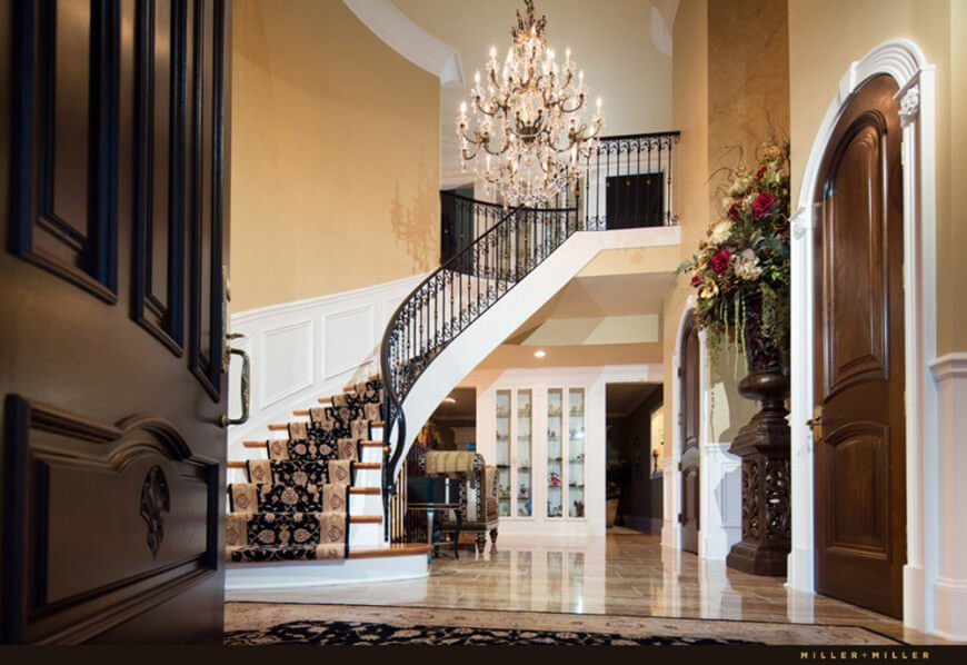 A dark wooden door opens to an elegant foyer with a curved staircase fitted with ornate steel railing and wooden treads dressed in a classy black runner.