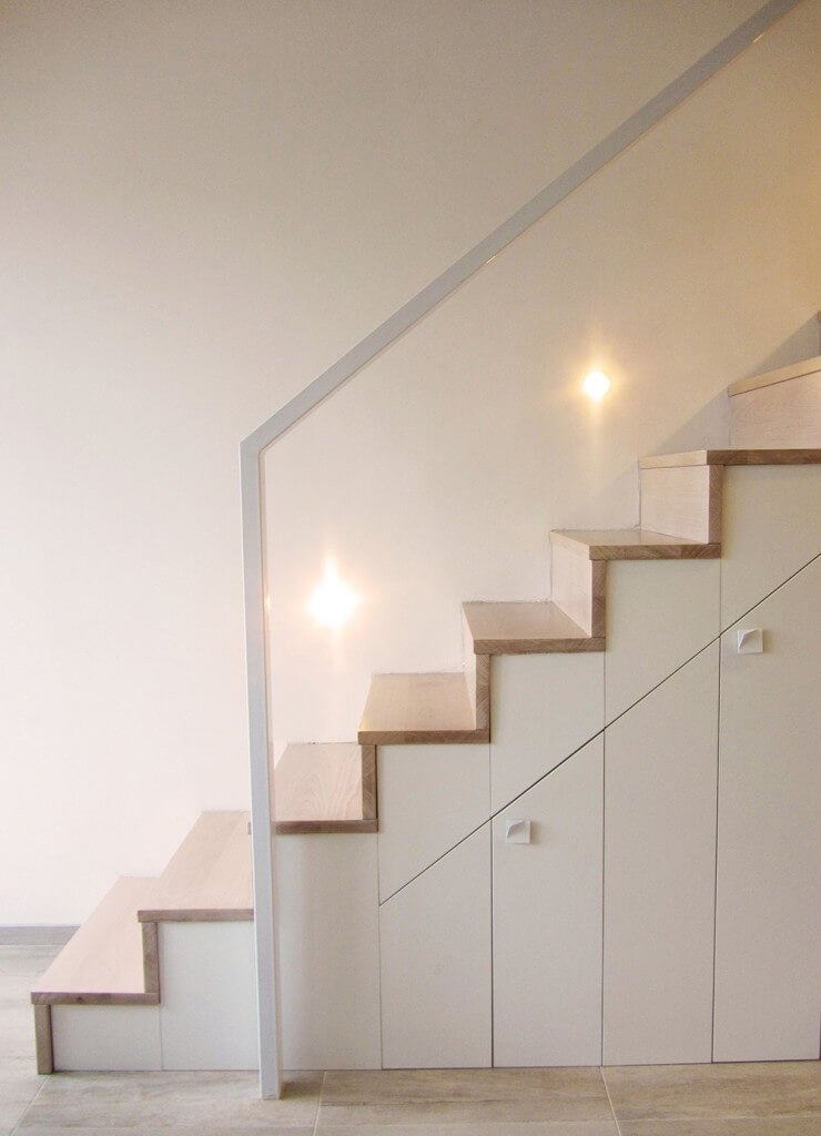 Straight staircase with stair lights and wood treads that complements with the hardwood flooring. It is framed with a glass balustrade lined with a white handrail.