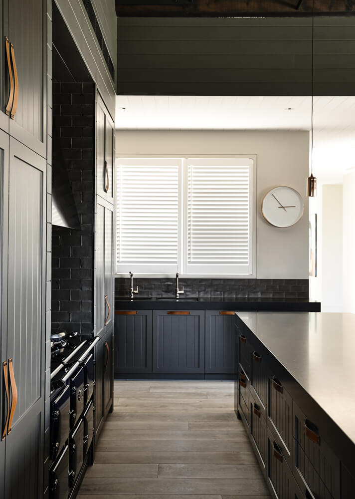 Dark kitchen features wood plank flooring and louvered windows with a round clock on the side. It includes black appliances that blend well with the dark gray cabinetry.