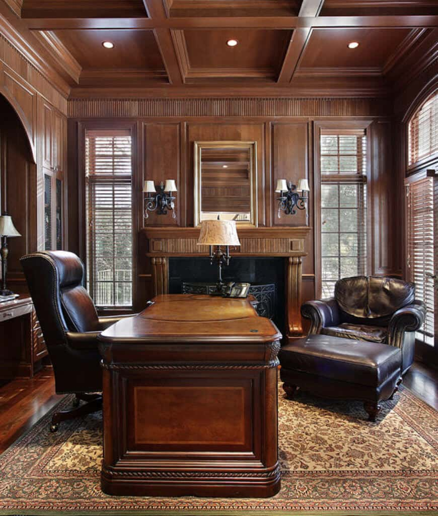 An all wood home office showcases a wooden desk paired with black leather chairs along with a vintage rug and fireplace in between louvered windows lighted by wrought iron sconces.