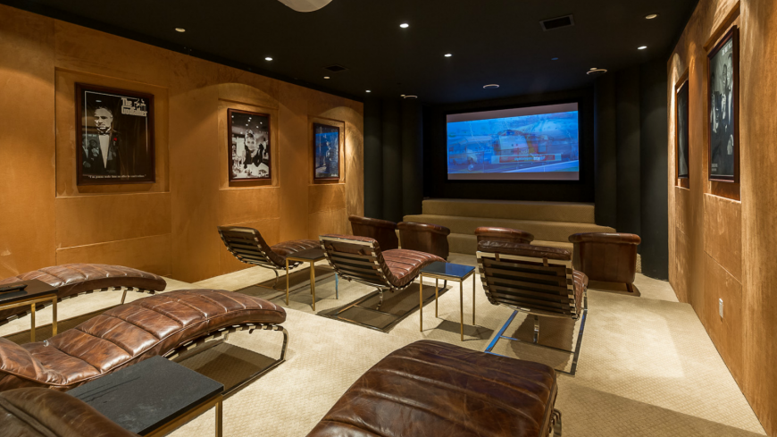 Large home theater featuring classic movies wall decor set on the brown walls together with an elegant black ceiling lighted by recessed lights. The seats look unique and charming.
