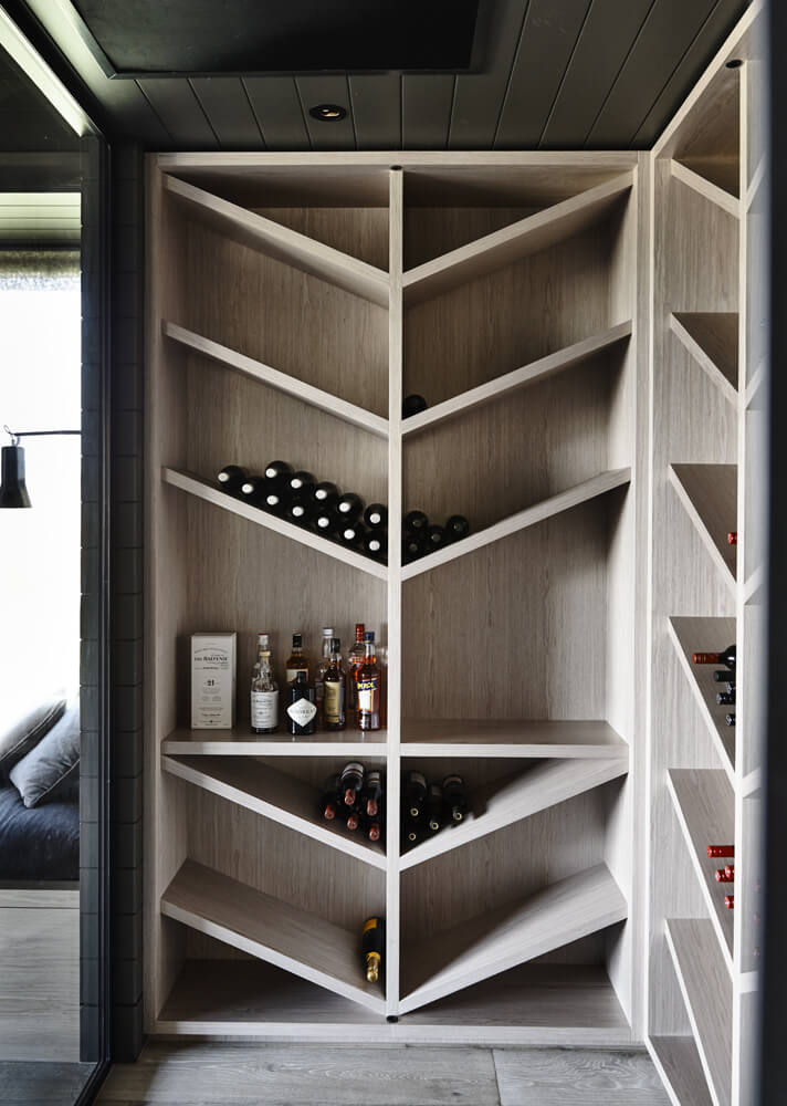 A corner wine cellar with light wood V-shaped wine shelves that complements the hardwood flooring. It has a black wood plank ceiling and walls.