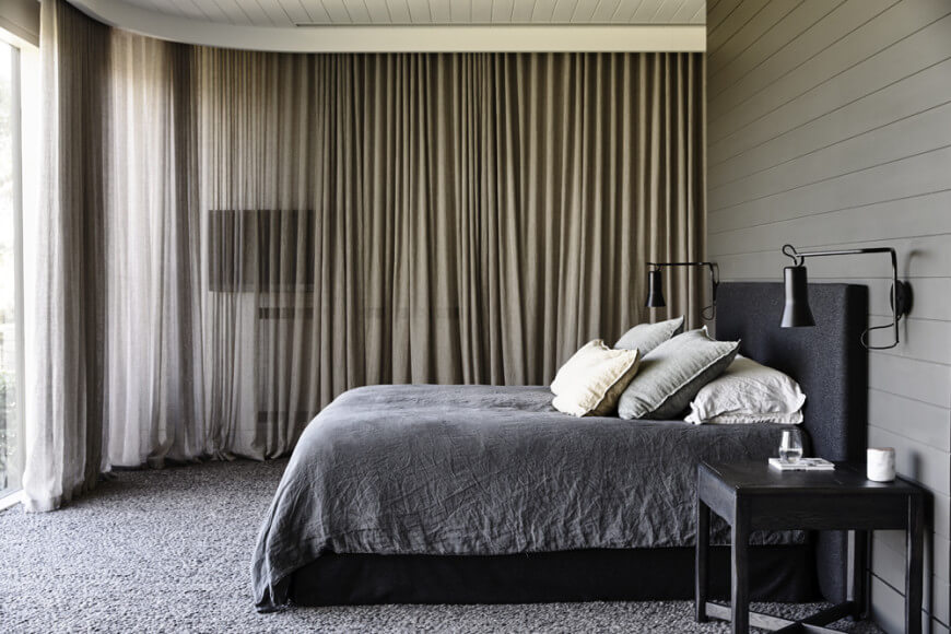 A close up look at this master bedroom's stylish gray bed with a black frame set on the carpet flooring.