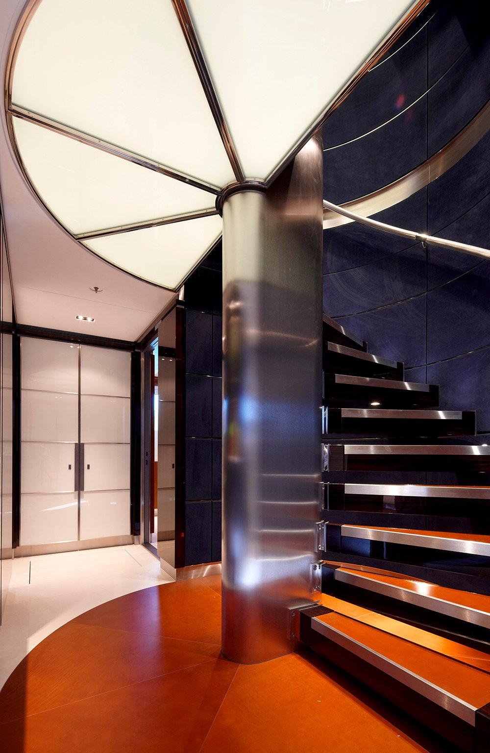 Luxurious entryway boasts a metal curved staircase accented with orange treads and fixed to the deep blue paneled walls.
