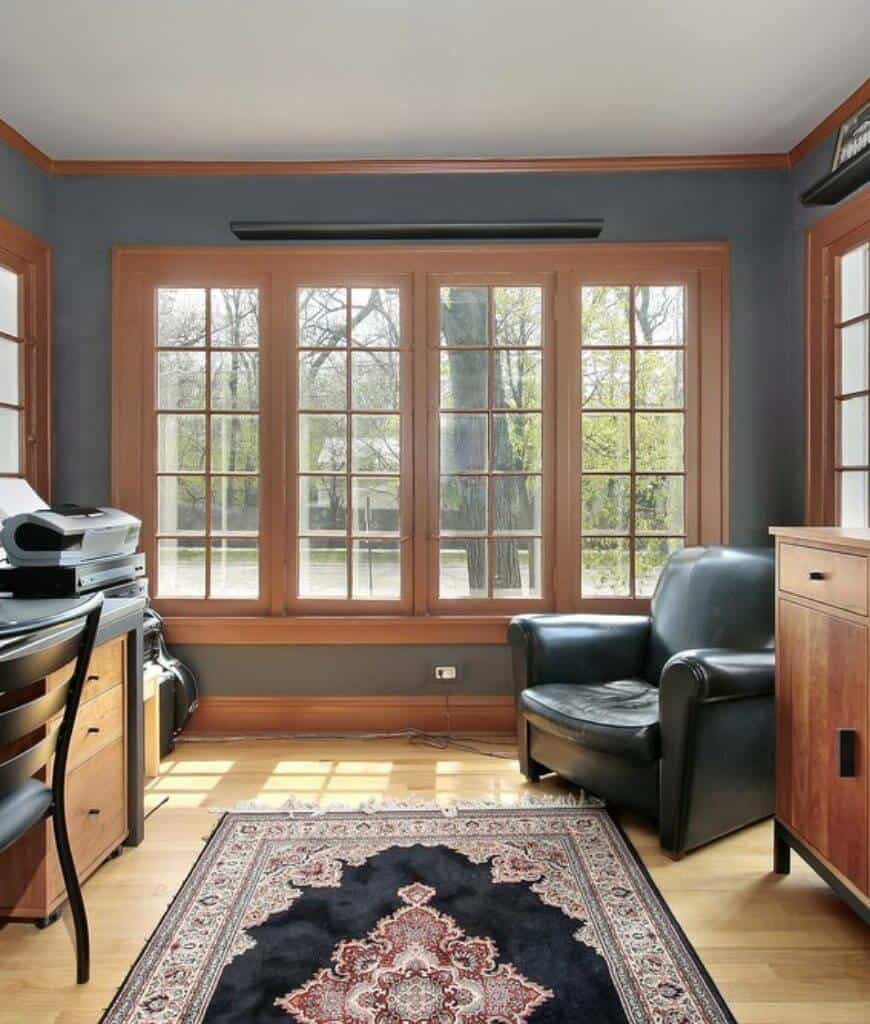 Airy home office with gray walls and light hardwood flooring topped by a tasseled rug. It includes wooden cabinets and black seats that complement with the floating shelves above the framed windows.