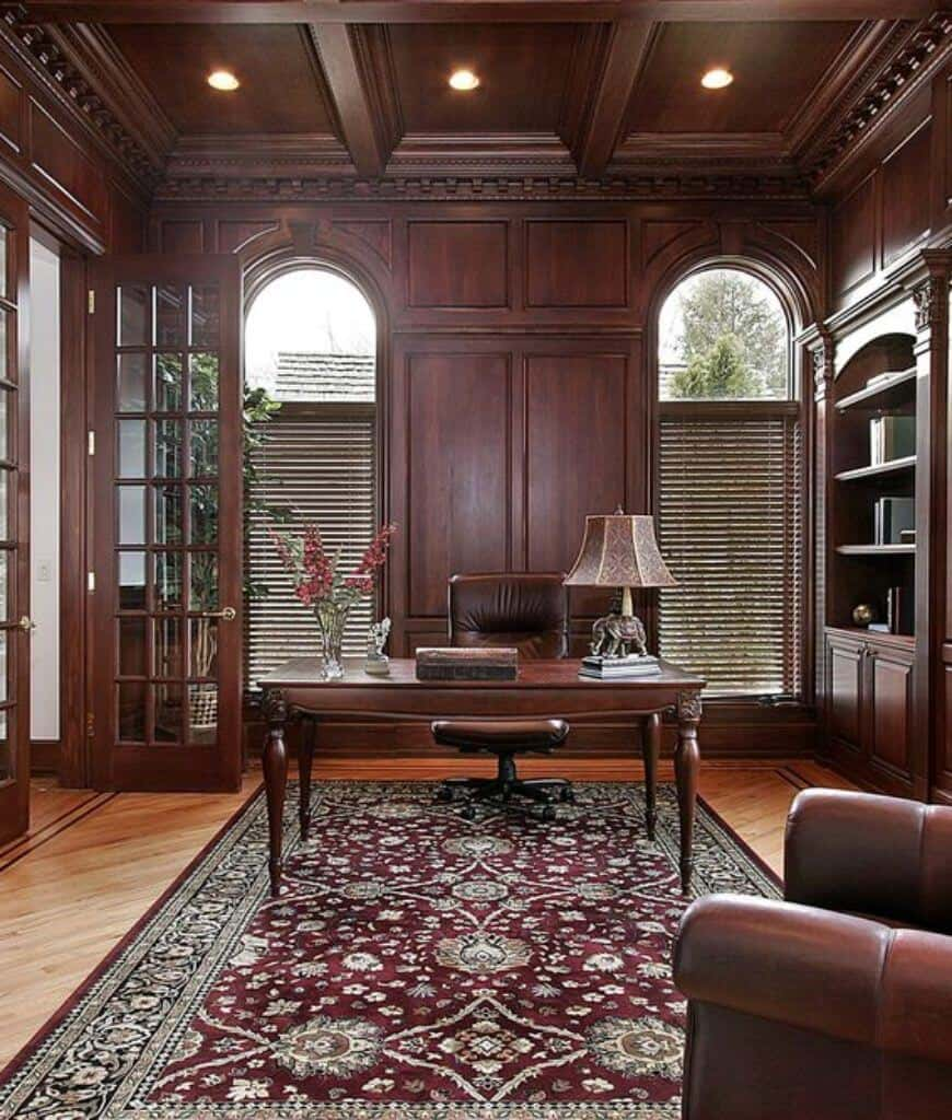 A French door opens to this home office with louvered windows and coffered ceiling fitted with recessed lights. It has a rectangular desk and leather swivel chair that sits on a red bordered rug.