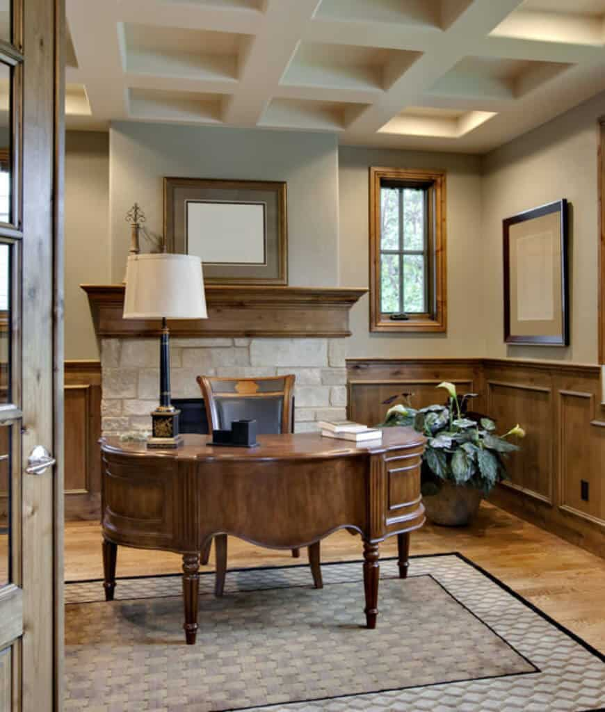 Craftsman home office with coffered ceiling and natural wood plank flooring topped by a geometric rug. It includes a carved wood desk and brick fireplace lined with a wooden mantel that complements with the wainscoting.