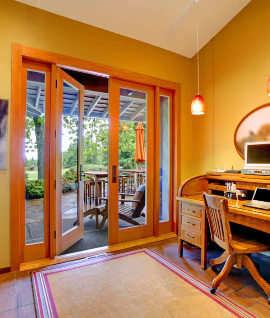 Warm home office features a bordered rug on terracotta flooring and a French door that opens to the patio. It includes a wooden desk and chair lighted by a glass pendant.