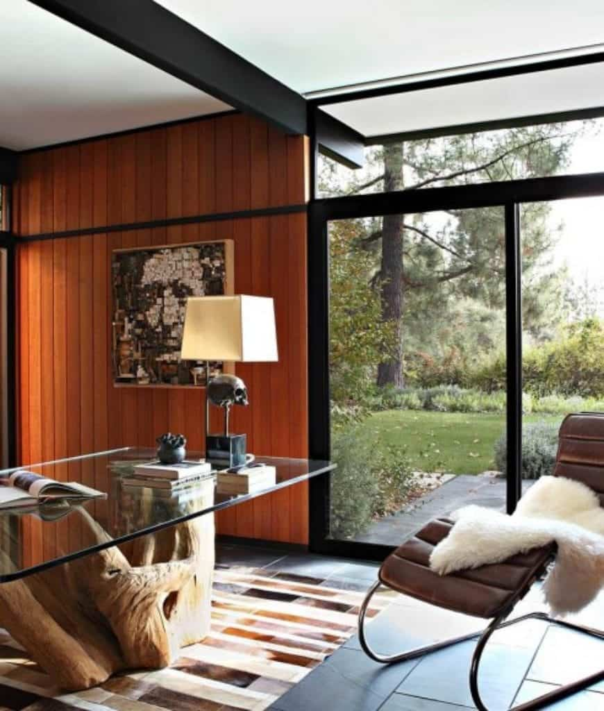 This home office is decorated with an amazing collage portrait mounted on the wood plank wall. It has a brown leather lounge chair covered with a faux fur blanket and a tree stump desk topped with glass and sits on a striking rug.
