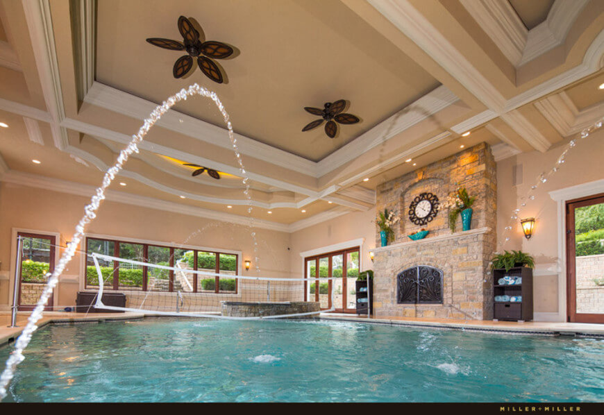 Large indoor swimming pool with a large fireplace under the stunning coffered ceiling.