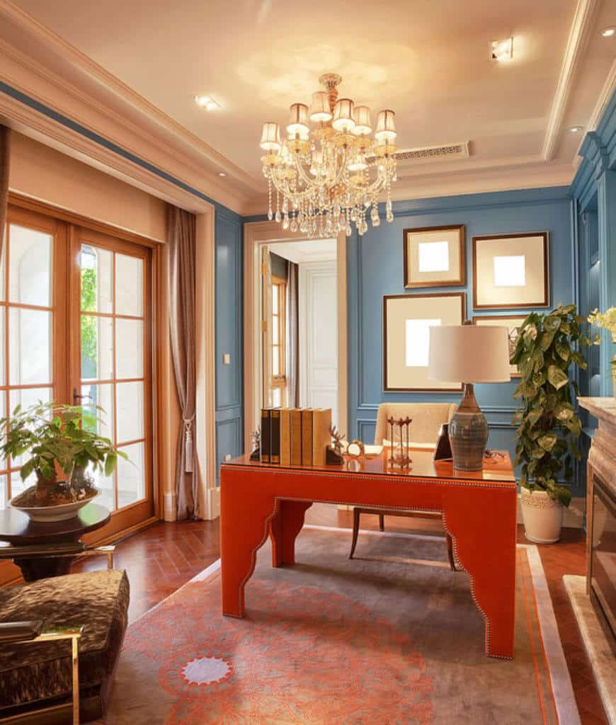 Fabulous home office designed with a gallery wall and fancy chandelier that hung over the wooden desk. It has blue wainscoted walls and herringbone wood flooring topped by an area rug.