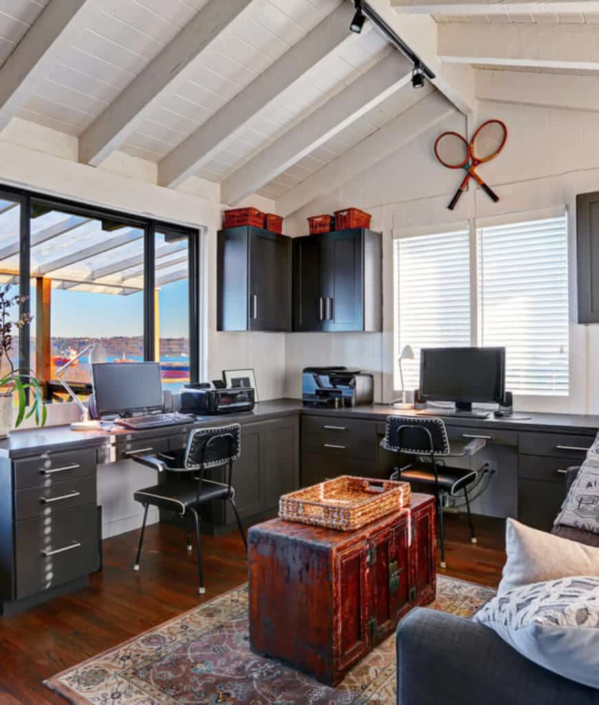 This home office boasts floating cabinets that match with the desks paired with black leather chairs. It is illuminated by track lights mounted on the white cathedral ceiling lined with wood beams.