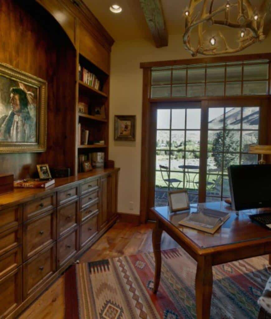 Rustic home office with built-in cabinet and a wooden desk on a patterned rug lighted by an antler chandelier that hung from the wood beam ceiling.