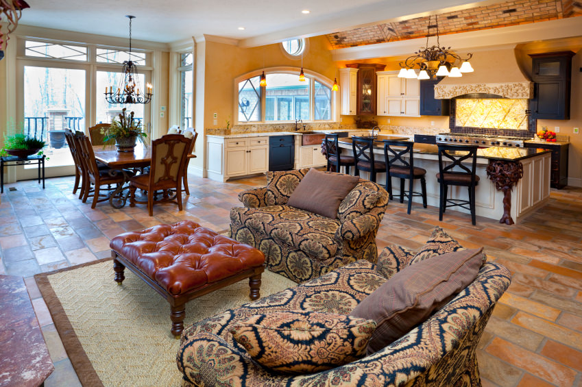This great room boasts a very classy set of seats in the living room and a glamorous kitchen lighted by a classy chandelier, along with a dining table set with a gorgeous chandelier lighting above.