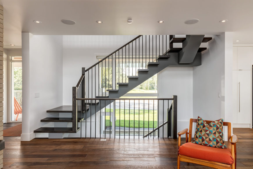 L-shaped riser-less staircase in a dark wood landing featuring wood and metal hand railing.