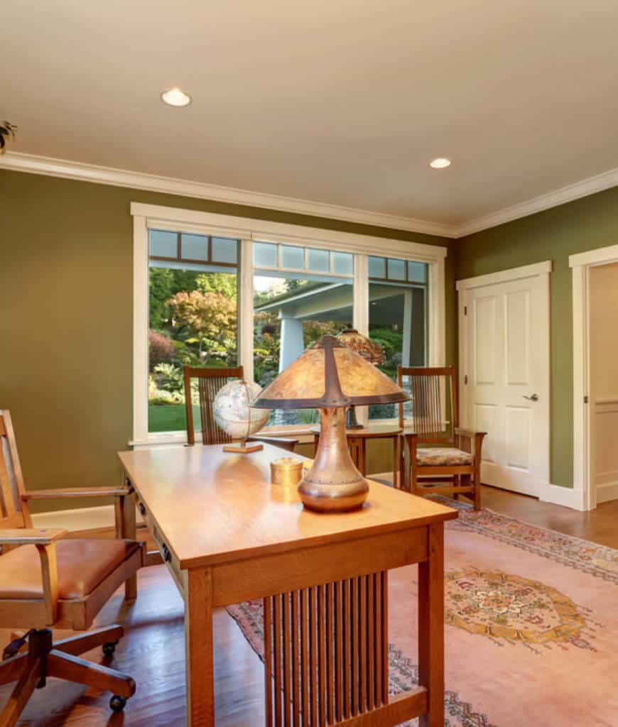 Green home office filled with wooden furniture and a charming pink rug that lays on the hardwood flooring.
