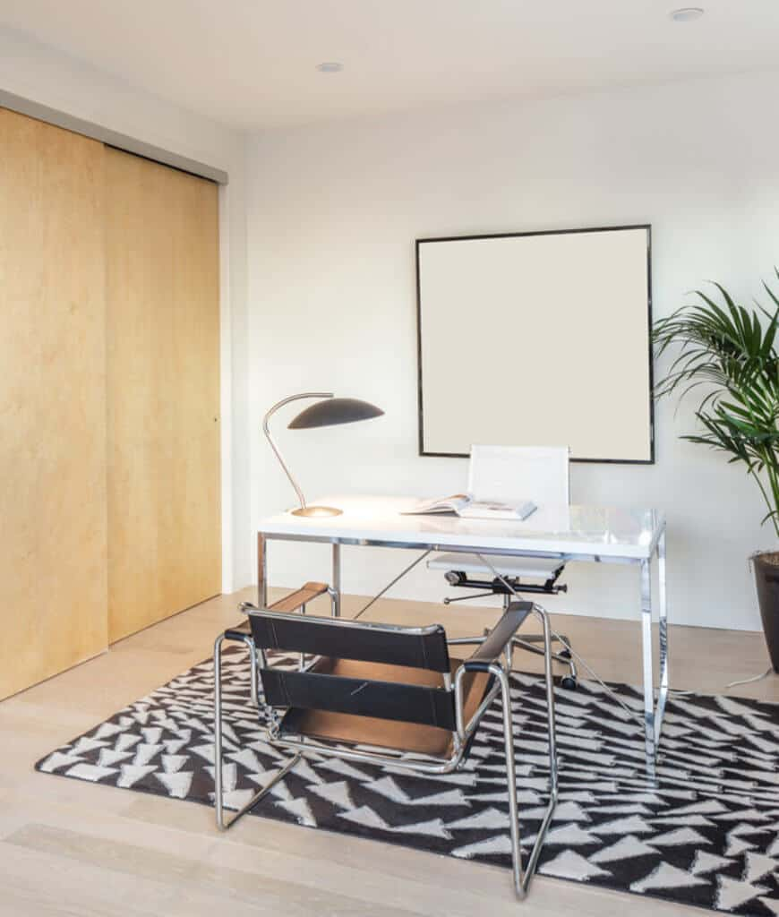 White home office beautifully contrasted with black area rug and leather chair accompanied by a metal desk and white swivel chair.