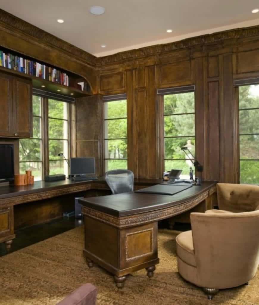 This home office features beige tufted chairs and built-in desks that blend with the wood paneled walls. It is illuminated by recessed ceiling lights along with natural light that flows through the framed windows.
