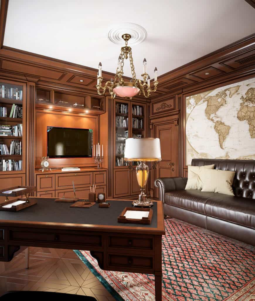 Cozy home office illuminated by a candle chandelier and table lamp that sits on a wooden desk. It has a leather tufted sofa and flat panel TV mounted in the middle of built-in cabinets.