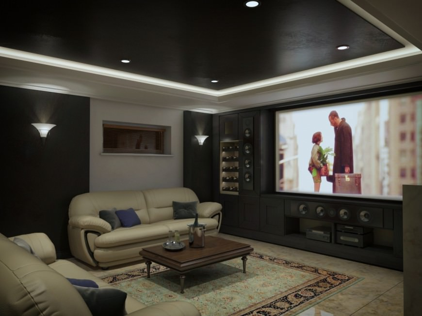 A cozy media room with a nice set of couches along with a widescreen TV in front. The espresso shade along with the wall lighting and tray ceiling are just so attractive together with each other.