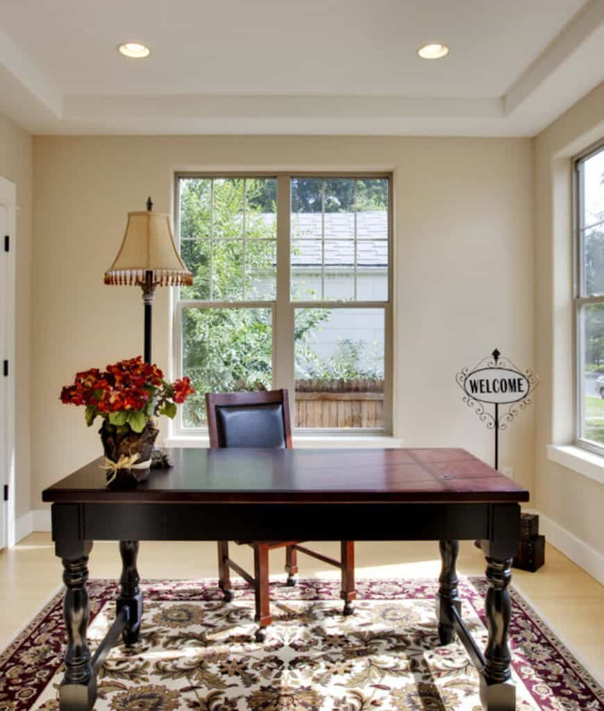 Beige home office designed with a welcome sign and lovely bordered rug that lays on the smooth hardwood flooring. It has a dark wood desk and chair illuminated by a table lamp and recessed lights fitted on the tray ceiling.