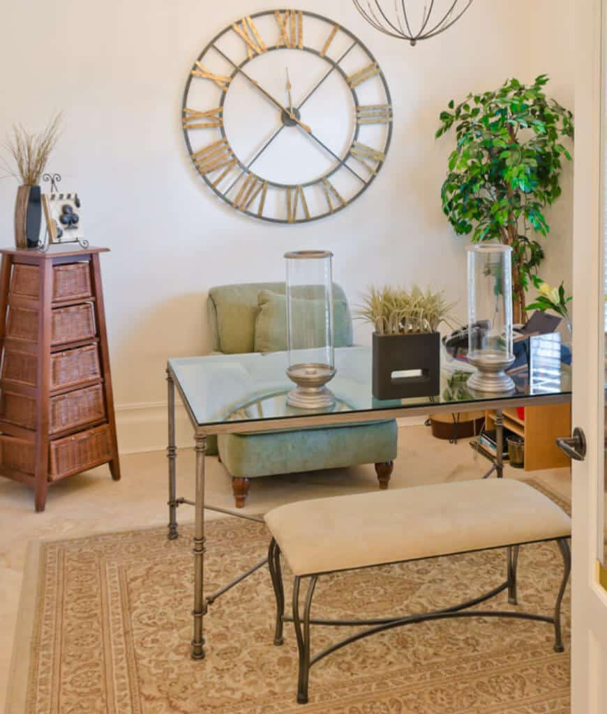 Fresh home office showcases an oversized wall clock along with a glass top desk and metal bench on a classic area rug.