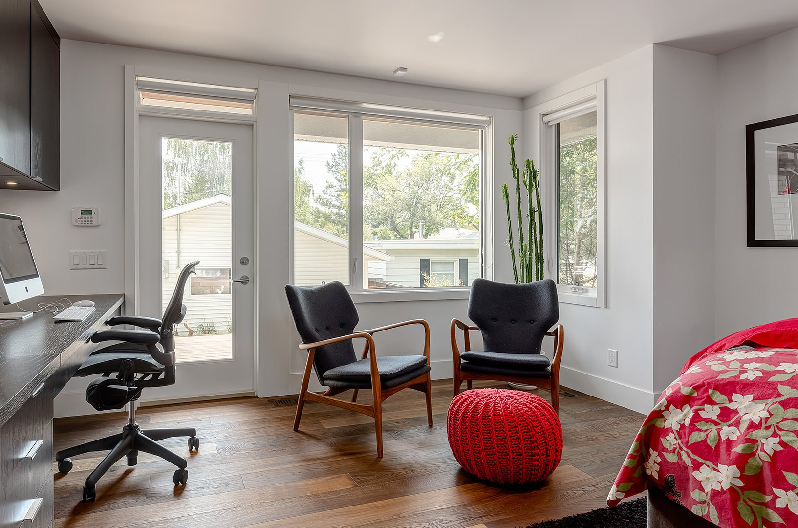 Airy home office with a seating area showcasing a pair of black wingback chairs and a red woven ottoman. It has a dark wood office desk with matching floating cabinets fixed on the white walls.