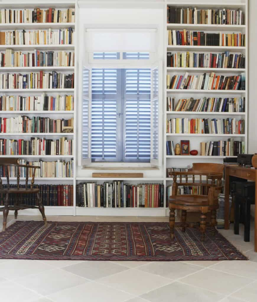 Home office with a tiled flooring topped by a tasseled rug and louvered windows surrounded with built-in bookshelves.